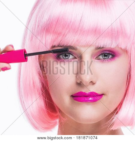 Portrait of girl with glamour make-up and pink hair using mascara isolated on white background