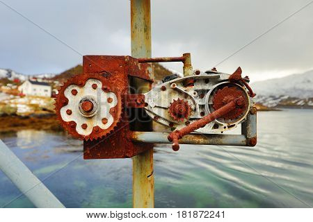 Old rusty ship winch against water close-up.