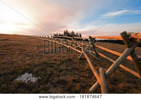 Split Rail Fence at dawn sunrise above Lost Water Canyon in the Pryor Mountains Wild Horse range on the Montana Wyoming state line USA