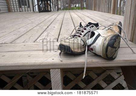 worn used garden shoes on the deck