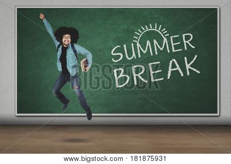 Afro guy holding book while leaping with summer break word on the chalkboard