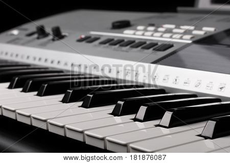 synthesizer keyboard with knobs and controllers on black background