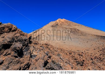 Mountain El Teide (Pico del Teide) the highest point of Tenerife and the Canary Islands with blue sky in the background .