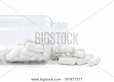 white medicine capsules spill out from clear bottle and isolated on white background with clipping path