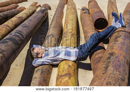 Young Man Dozed Off, Lying On Metal Pipes