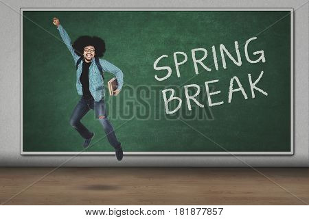 College student holding book while leaping with spring break text on the chalkboard