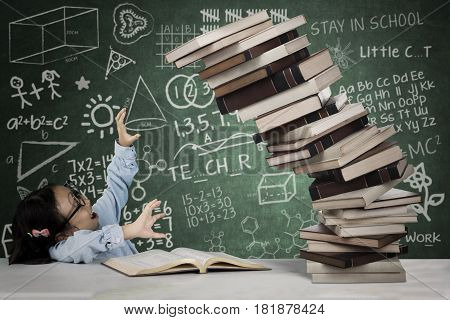 Picture of cute schoolgirl holds a pile of falling book with doodles on the chalkboard