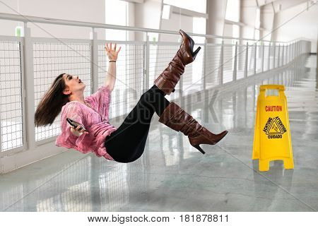 Young businesswoman falling on floor inside office building