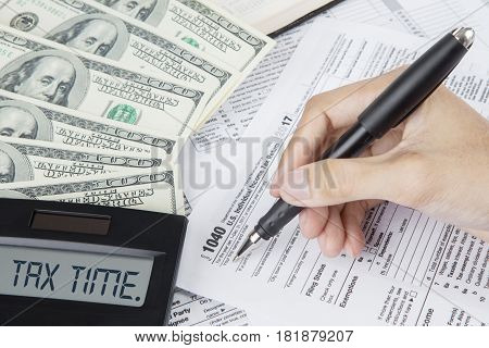 Portrait of male worker's hand with dollar money and text of tax time on the calculator while writing on a tax form