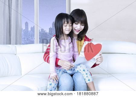 Beautiful young mother and her daughter sitting on the sofa while reading a letter for mothers day