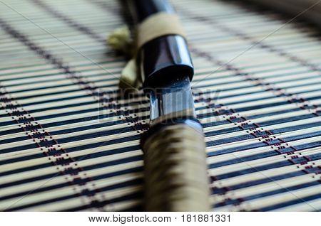 Japanese Sword Katana On Bamboo Mat. Selective Focus