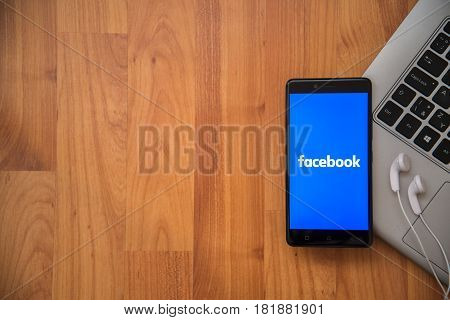Los Angeles, USA, april 16, 2017: Facebook application on smartphone with earphones and notebook on wooden background.