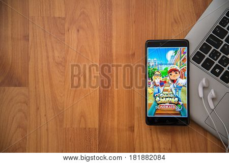 Los Angeles, USA, april 16, 2017: Subway surfers application on smartphone with earphones and notebook on wooden background.