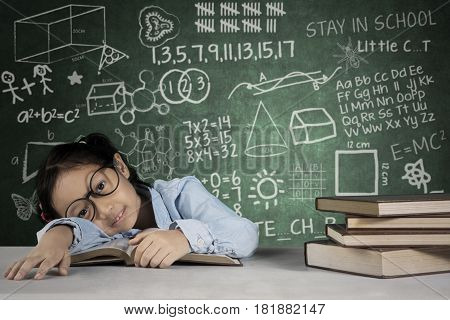 Image of schoolgirl looks bored while studying in the classroom with doodles on the chalkboard