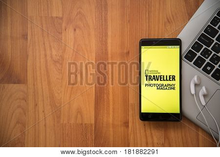 Los Angeles, USA, april 16, 2017: National geographic traveller photography magazine application on smartphone with earphones and notebook on wooden background.