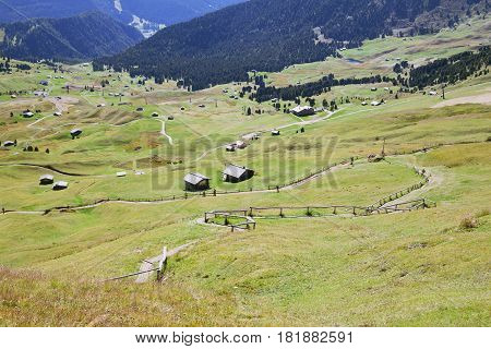 Valley with houses in Dolomite Alps, view from a mountain