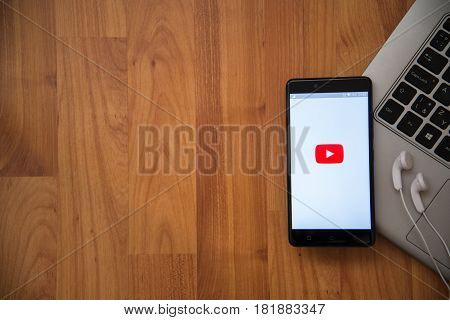 Los Angeles, USA, april 16, 2017: Youtube application on smartphone with earphones and notebook on wooden background.