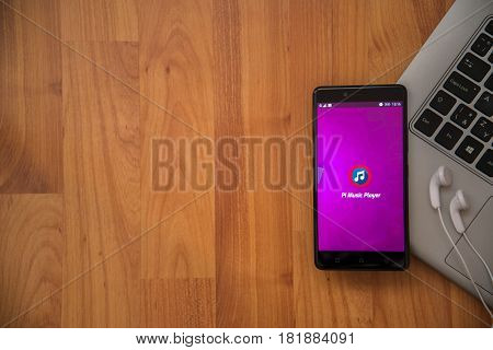 Los Angeles, USA, april 16, 2017: Pi Music player application on smartphone with earphones and notebook on wooden background.