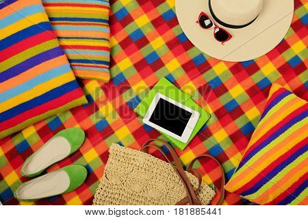 Summer picnic. Electronic book hat and bag on the picnic mat. Selective focus.