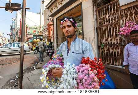 BANGALORE, INDIA - FEB 12, 2017: Street vendor selling hoops with artificial flowers for girls on February 12, 2017. Capital of the state Karnataka has a population of 8.42 million