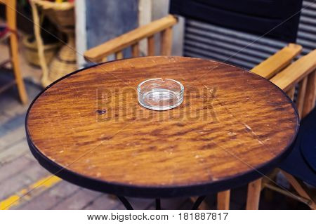 glass ashtray on the brown wooden table