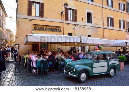 ROME ITALY - APRIL 10 2017: People eating traditional italian food in outdoor restaurant Carlo Menta in Trastevere district in Rome Italy on April 10 2017.