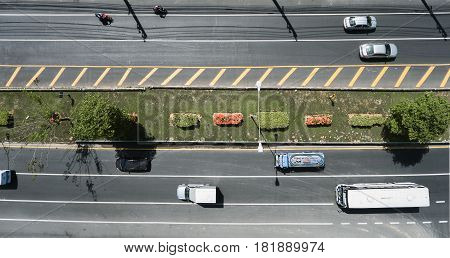 Aerial view of the wide road with a nice dividing strip of grass flowers and trees. Top view of moving cars and buses. Flat illustration of road traffic.