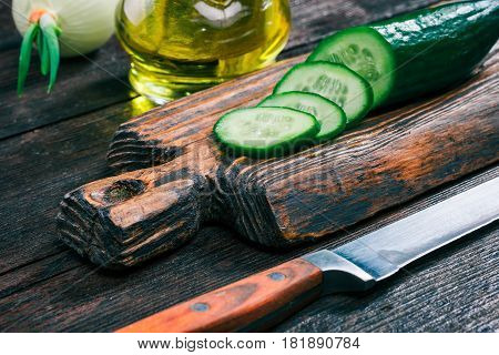 Fresh sliced cucumber and onions on rustic wooden cutting board and olive oil in cruet on old dark wood table. Close-up angle view