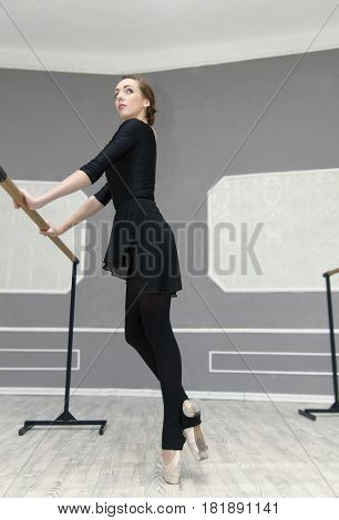Pretty Young Graceful Ballet Dancer Warms Up In Ballet Class. On Tiptoe Near The Ballet Bar