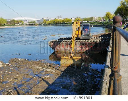 CLUJ-NAPOCA ROMANIA - APRIL 1 2017: River dredging with tracked excavator. Water body maintenance gathering deposited sediments with dredging bucket.