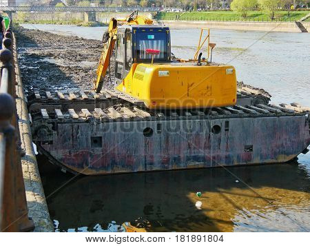 CLUJ-NAPOCA ROMANIA - APRIL 1 2017: Tracked excavator dredging riverbed. Water body maintenance gathering deposited sediments with dredging bucket.