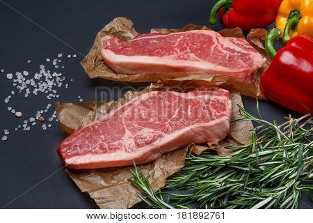 Two pices of New York steak with vegetables, salt and rosemary