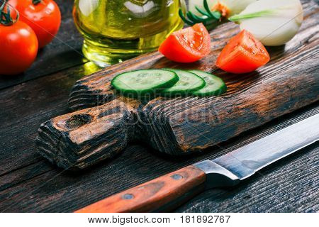 Fresh sliced cucumber, tomatoes and onions on rustic wooden cutting board and olive oil in cruet on old dark wood table. Close-up angle view