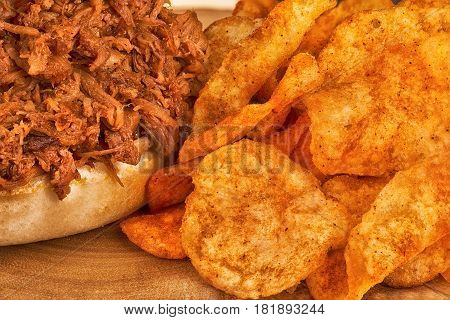 Close up on pulled pork sandwich and potato chips.