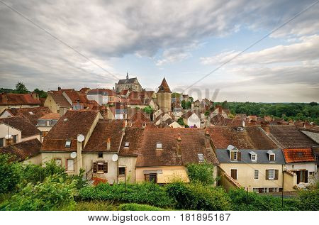 View of the small town of Saint-Florentin. Burgundy. France. Tiled roofs of houses are visible. In the background is St. Florentine's Cathedral.