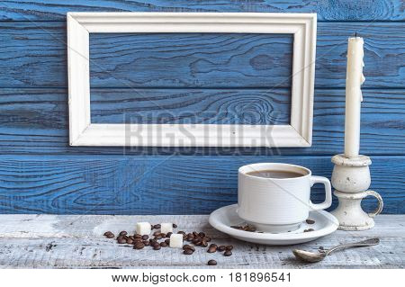 White frame coffee cup and a candel on a background of blue boards