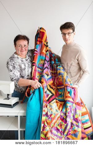 quilting in the workshop of tailors - male and female smiling tailors held together in hands a large bright quilt, sewn from scraps of colored fabric on the sewing machine. Family hobby concept.