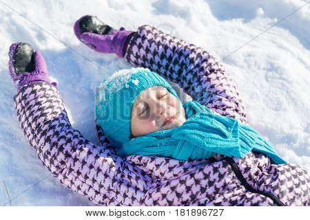 Top view of cute girl lying on snow