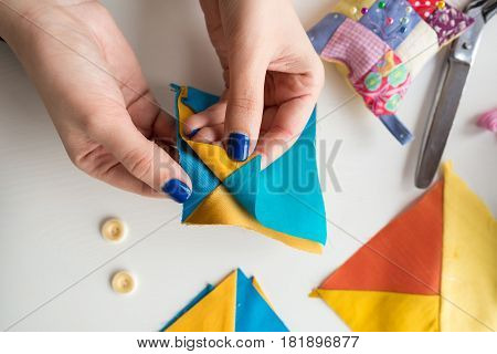 needlework and quilting in the workshop of a young tailor on white background - close-up on hands of a tailor holding scraps of fabrics lying on a white table with buttons, pin cushion, scissors