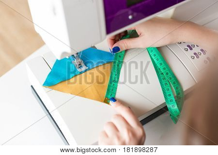 needlework and quilting in the workshop of a tailor - closeup on hands of a tailor woman working on sewing machine with measuring tape and pieces of stitched in blue and yellow fabrics