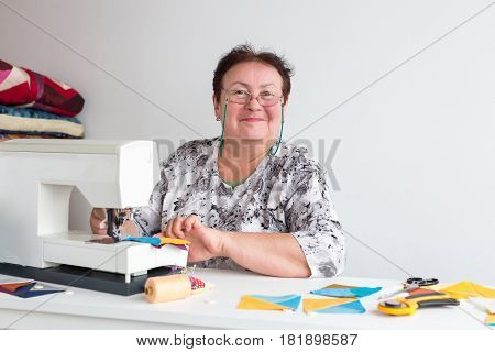 patchwork and quilting in the workshop of a tailor woman on white background - elderly woman with glasses sews on the sewing machine scraps of blue and yellow fabric for patchwork