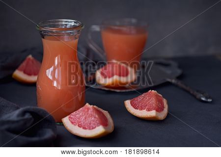 Glass of freshly squeezed grapefruit juice with fresh citrus fruits on dark background.