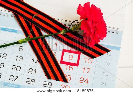 9 May card - red carnation and George on the calendar with framed 9 May date. Concept of 9 may Victory Day