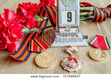 VELIKY NOVGOROD RUSSIA - CIRCA APRIL 2017.9 May card - vintage metal desk calendar with 9 May date medals George ribbon red carnations bouquet - Victory day 9 May concept. Selective focus at the calendar