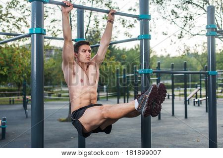 Young fitness man doing hanging leg raises exercise working out his abs in the park