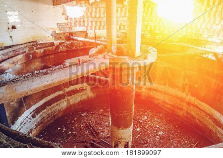 Inside an abandoned factory, a shop with a circular capacity and destroyed walls, sunlight filter effect
