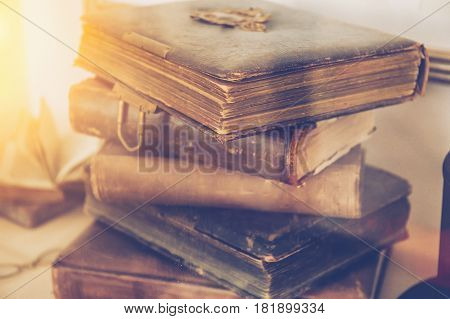 Stack of ancient old antiquarian books, toned photo with vintage filter and sun light effect