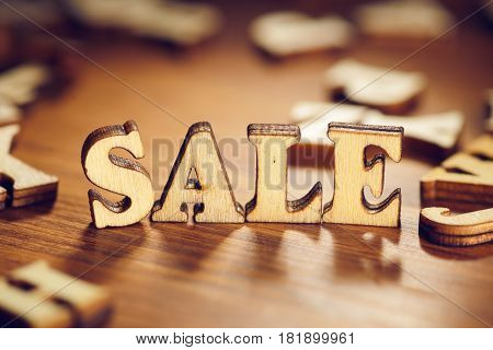 Sale word made from letters on wood plank table. Macro shot