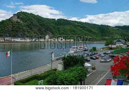 Sankt Goar, Germany - July 8, 2011: View from hotel window on Sankt-Goar embankment and Snak Goarshausen medieval village and Rhine vineyards on of the hills in Germany.