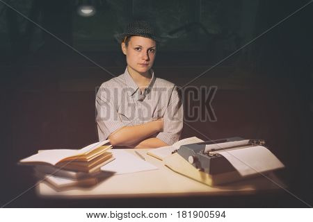 Portrait of a girl in a hat sitting at a table with a typewriter and book think about the idea at night